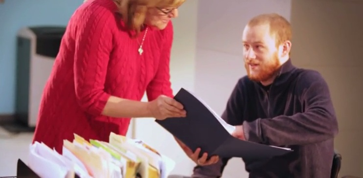 Staff member and a consumer reviewing a file folder.