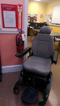A wheelchair, an evacuation map, and a fire extinguisher.