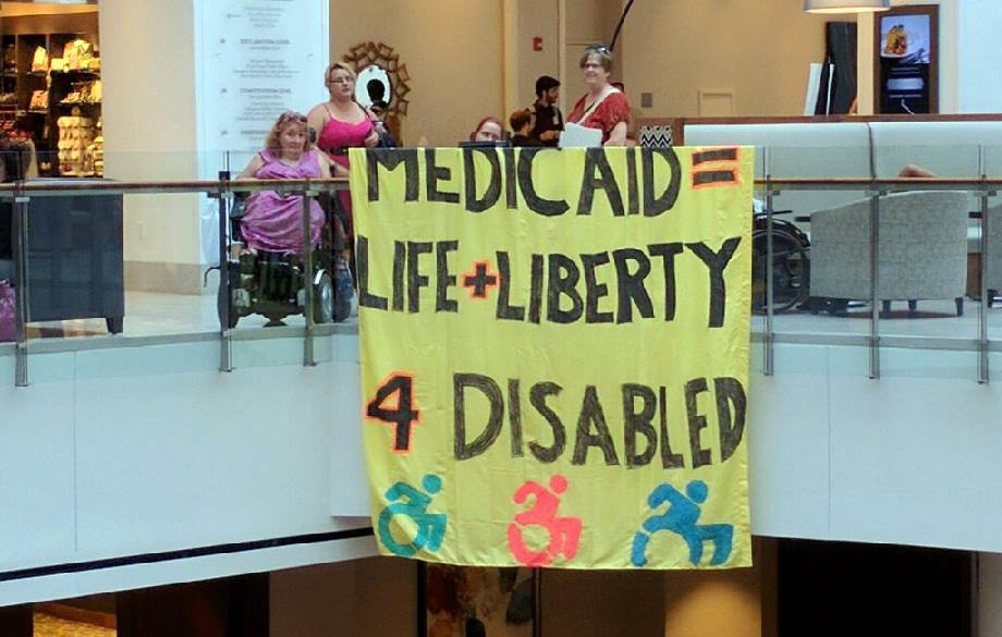 "This banner that says ""Medicaid = Life + Liberty 4 Disabled, and also features the universal access symbol in bright colors was created by TRPIL staff for use at NCIL 2017"