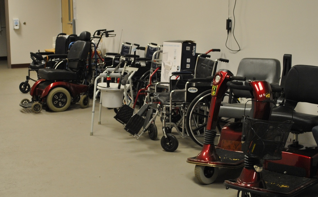 Donated wheelchairs and other AT equipment lined up against a wall.