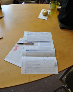 A voter registration form on a desk, ready to be filled out by a waiting pen.