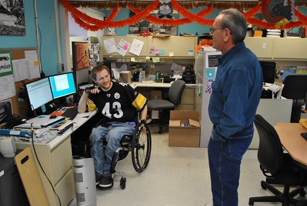 Standing employee speaking with an employee in a wheelchair